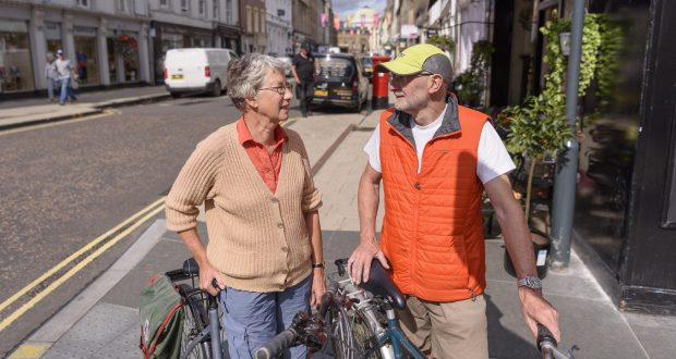 Older working people stand next to their bicycles