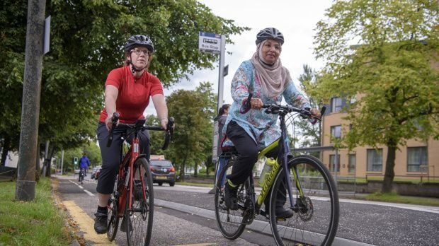 Two women cycle along a segregated cycle path into the city