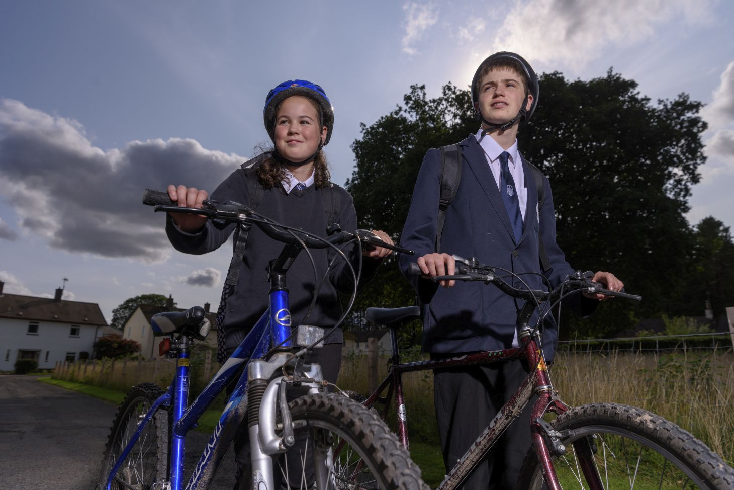 2 school children stand with their bikes