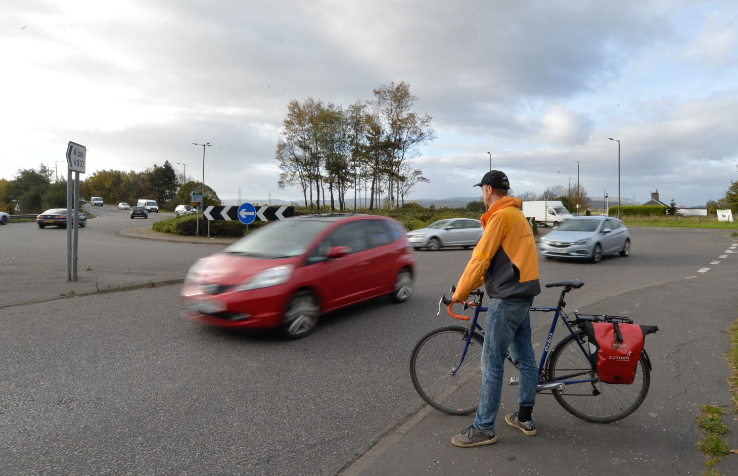 Cyclists waiting to cross road near roundabout