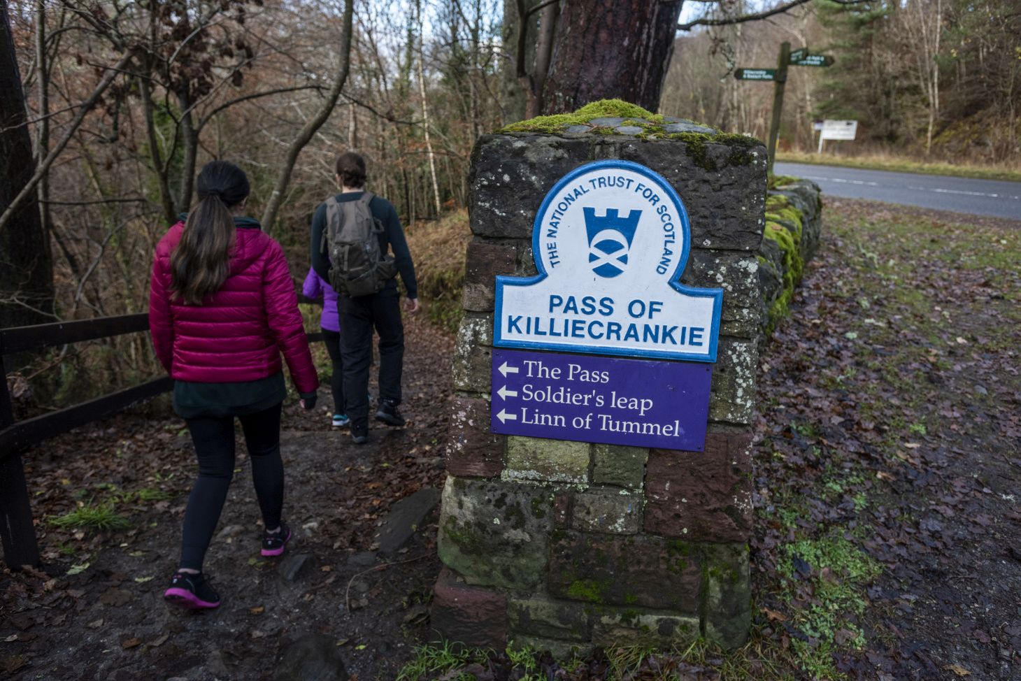 """3 people walking along woodland path with their backs to the camera. A sign in the foreground reads """"The national trust for Scotland. Pass of Killiecrankie"""""""